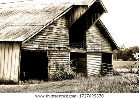 black and white photo of front of old barn , tin roof