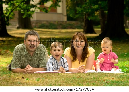 A portrait of a happy family lying on the grass in a park. #17277034
