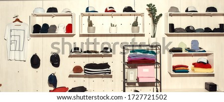 Custom apparel, clothes neatly arranged or folded on shelves. Stack of colorful clothing and baseball caps in the store. Horizontal shot
