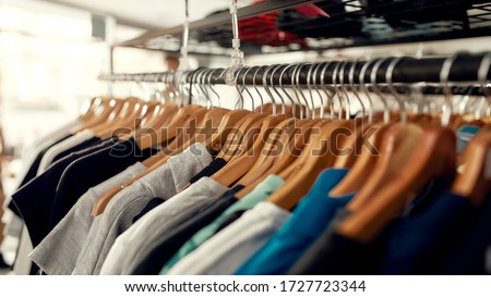 Close up of clothes rack or rail in the store. Items at custom T-shirt, clothing printing company. Horizontal shot. Selective focus