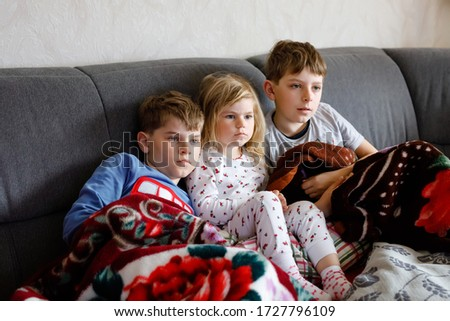 Cute little toddler girl and two school kid boys watching cartoons or movie on tv. Three happy healthy children, siblings during coronavirus quarantine staying at home. Brothers and sister together.