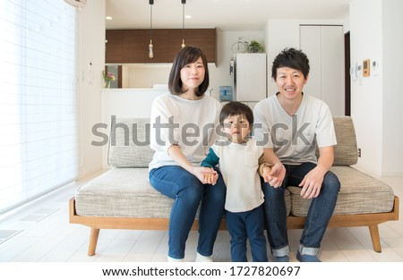 Family of three relaxing in the living room #1727820697