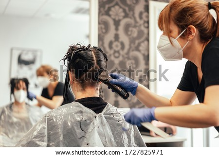 Hairdresser with mask shaving with razor. Reopening with security measures of Hairdressers in the Covid-19 pandemic Royalty-Free Stock Photo #1727825971