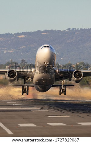 Large twin engine commercial airplane taking off from an international airport runway.
