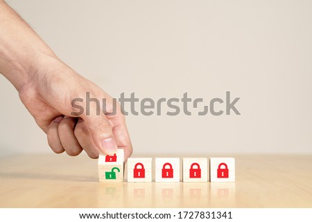 Man's hand turning wooden box red key lock to green unlock key. Start unlock lockdown after coronavirus covid-19 pandemic or epicdemic crisis. Time to reopening, relunch or restart concept #1727831341