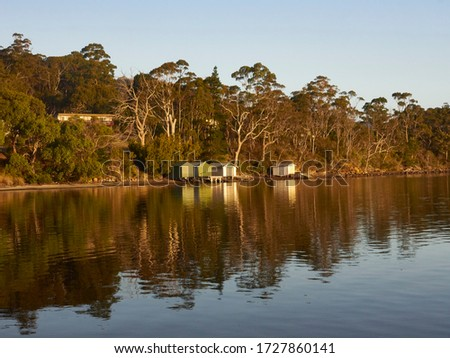 Nubeena  Tasman Peninsula sun hitting the boat sheds on the bay.  Golden colours of the trees behind all reflecting on the sea water      #1727860141