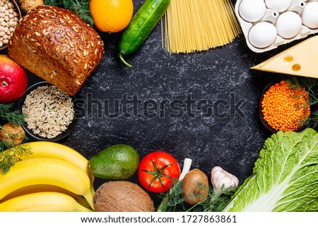 Dietary balance picture with fruits, vegetables and seeds on black stone background