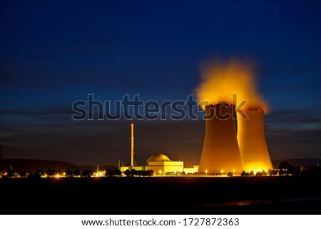 Night shot of a nuclear power plant close to a river with blue night sky. Royalty-Free Stock Photo #1727872363