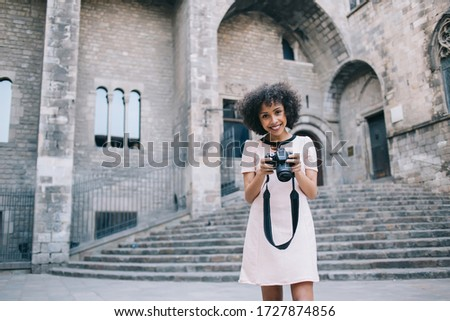 Happy African American female with photo camera smiling and looking at camera while standing outside ancient building with weathered steps on street of Barcelona City #1727874856