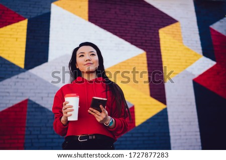 Pensive Asian youngster with takeaway cup and mobile phone thinking at urban setting with street art, trendy dressed generation Z holding cellular gadget and coffee to go spending leisure in city Royalty-Free Stock Photo #1727877283