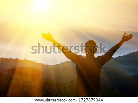 Man with arms raised at sunset. Young man at sunset raises his hands up #1727879044