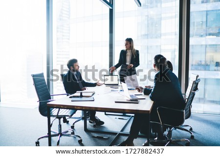 High angle of content female entrepreneur in elegant clothes explaining business strategy to board of directors while standing near table during meeting #1727882437