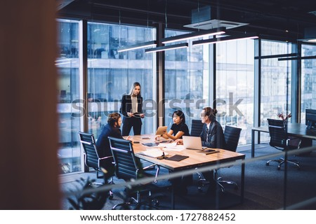 From above of group of diverse colleagues in formal clothing discussing business ideas while gathering at table in modern office and working together Royalty-Free Stock Photo #1727882452