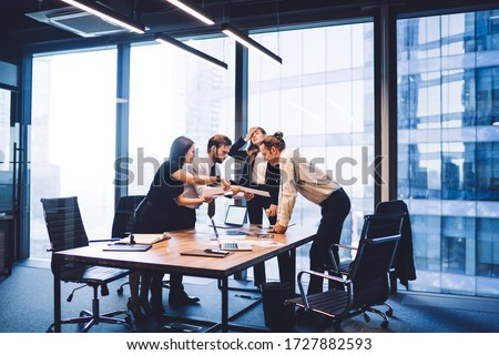 Male and female professionals teamworking during brainstorming cooperation on paper documents, group of diverse employers discussing corporate investment of firm capital briefing in conference room #1727882593