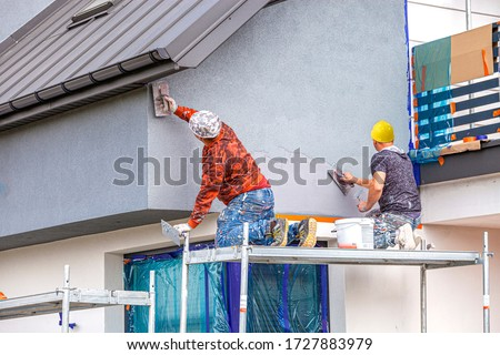 Construction workers plaster the facade of the house. Application Of Facade Plaster. #1727883979