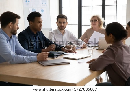 Confident african american businessman talking with young and mature colleagues in boardroom at meeting. Black coach mentor speak with partners negotiating about business project at conversation. #1727885809