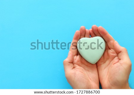 male hand holding heart over blue background. copy space, top view Royalty-Free Stock Photo #1727886700
