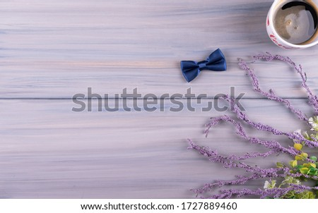 Happy birthday greeting card concept father's day or anniversary on wood table background, Bow tie, coffee cup,  with flowers. Top view.