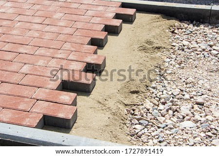 Process of construction of brick paved sidewalk, half built pavement road #1727891419