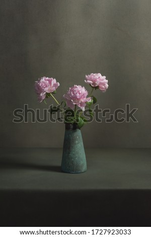 Pink peonies in a vintage pottery vase on a table in a grey room. #1727923033