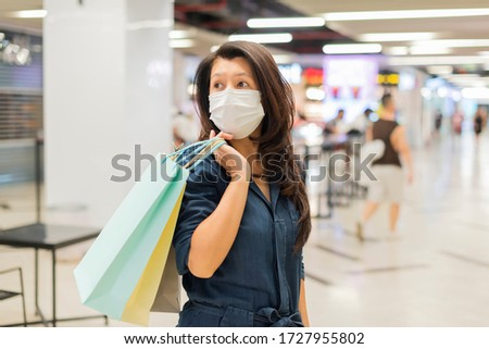 Asian woman holding paper bags and wearing a hygiene protective mask over her face while walking at the crowded shopping mall. Healthcare and prevention from coronavirus in crowded place. Copy space #1727955802