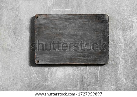 Dark gray wooden empty board hanging on shabby concrete cement wall. Place for logo, sign or text.