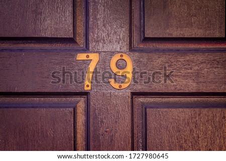 House number 79 on a dark wooden front door