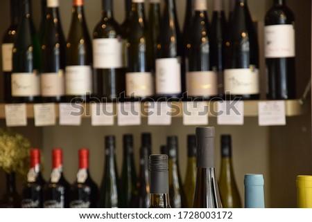 Wine bottles on wooden shelf in wine store #1728003172