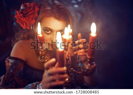 Bewitching woman fortune-teller witch looking at the camera through the flame of candles. Sepia vintage portrait. #1728008485