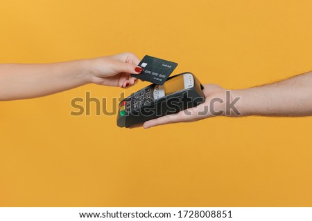 Close up cropped photo of female and male hold wireless modern bank payment terminal to process acquire credit card payments isolated on yellow background. Money, achievement, career wealth concept #1728008851