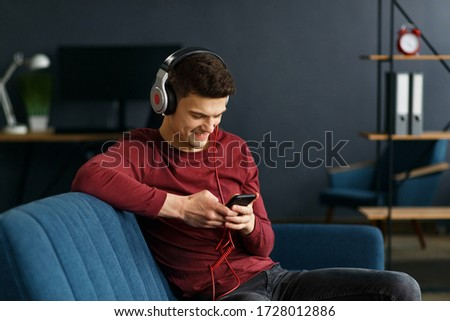 Enjoy listening to music.Young man in headphones listening music on smart phone using music app. Portrait of guy in earphones and mobile phone at home. Relaxation, leisure and stress management. #1728012886