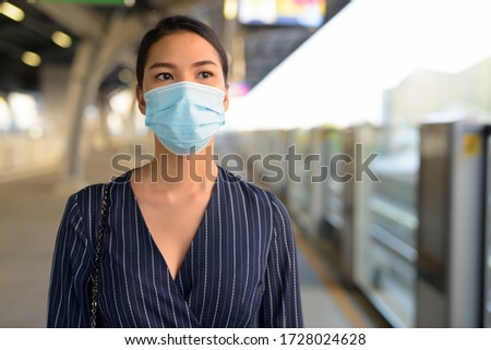 Young Asian businesswoman waiting with mask for protection from corona virus outbreak at the skytrain station #1728024628
