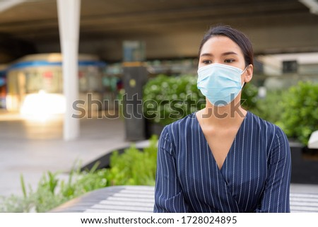 Young Asian businesswoman with mask for protection from corona virus outbreak thinking and sitting in the city #1728024895
