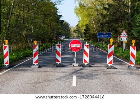 Travel restrictions, borders closure, borders closed during Covid or Coronavirus lockdown, stop sign on the road  Royalty-Free Stock Photo #1728044416