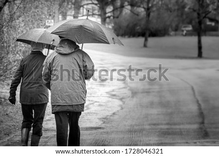Two older people walking the street in rainy weather. Black and white picture.