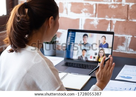 Young Asian businesswoman work at home and virtual video conference meeting with colleagues business people, online working, video call due to social distancing at home office Royalty-Free Stock Photo #1728055387