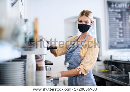 Coffee shop woman owner working with face mask, open after lockdown quarantine. #1728056983