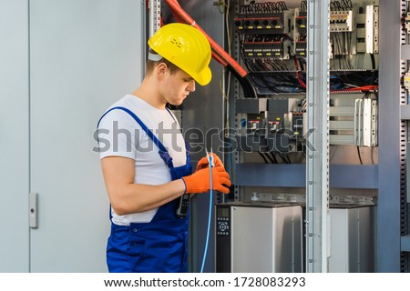 A young electrician in a yellow hard hat cuts the blue wire with pliers. An employee maintains a switchboard at the factory. Indoor. #1728083293