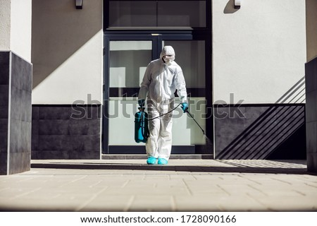 Full length of man in sterile uniform and mask sterilizing surface outdoors from corona virus, fungus and disease. Royalty-Free Stock Photo #1728090166