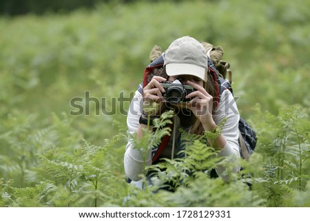 Young woman taking pictures during walk in nature