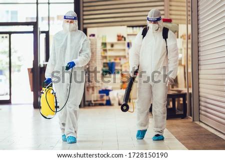 Professional workers in hazmat suits disinfecting indoor of mall, pandemic health risk, coronavirus #1728150190