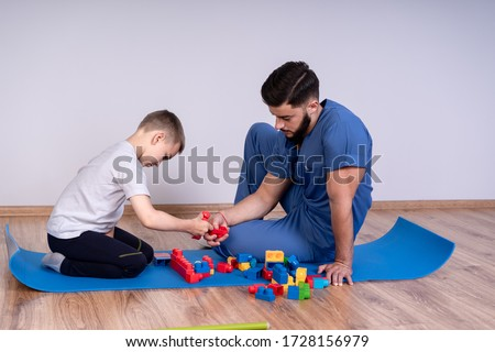Male doctor with boy patient play educational game designer, the concept of rehabilitation of children.