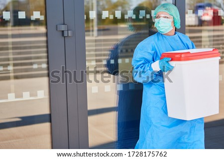 Doctor or surgeon with organ transport after organ donation for surgery in front of the clinic in protective clothing Royalty-Free Stock Photo #1728175762