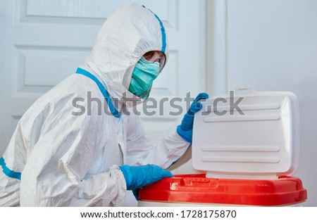 Surgeon in protective clothing in clinic before heart transplant with organ donation after transport in a box Royalty-Free Stock Photo #1728175870