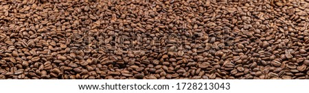 Super large high resolution panorama macro photography of a huge heap of coffee beans. Close up to thousands of roasted coffee beans. Brown roasted beans after roast. Background  wallpaper image