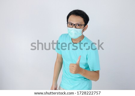 Young Asian Man wear medical mask is give ok hand sign with confident gestures. Indonesian man wearing blue shirt. #1728222757