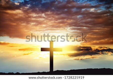 Cross against the sky . Dramatic nature background . Light from sky . Religion background .  Royalty-Free Stock Photo #1728225919