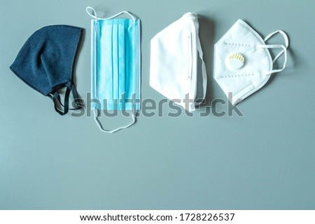 Different protective masks on blue background with copy space. Reusable fabric mask, disposable medical mask, facemask respirator with breathing valve. Right choosing for protection. Virus protection Royalty-Free Stock Photo #1728226537