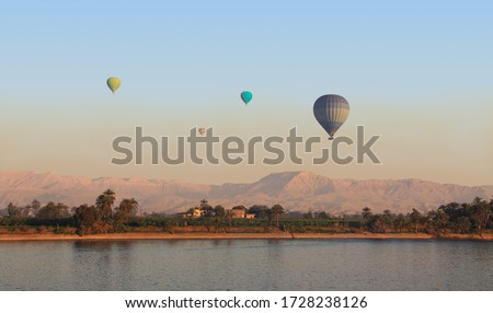 Several hot air balloons in the air early in the morning over the area of Thebes in Upper Egypt. In the foreground the Nile and in the background the mountains with the famous Valley of the Kings. #1728238126