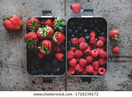 Healthy summer vegan lunch. Flat-lay of fresh seasonal strawberries, raspberries, blueberries and blackberries in lunchboxes over grey background, top view. Vegan, vegetarian, clean eating, detox food #1728238672